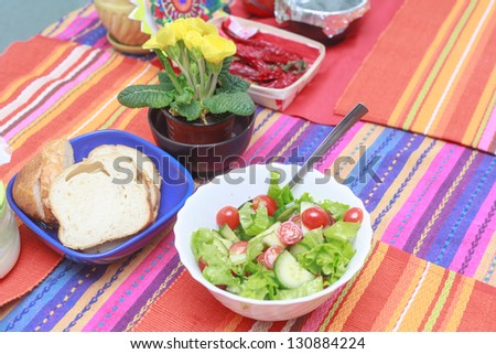 A green salad in a stylish white bowl. With rocket leaves cherry tomatoes spanish onions and capsicum. Flowers ? red pepper and bread on the table too - stock photo