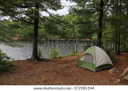 A green tent setup right beside a lake.  Shot in Algonquin Provincial Park, Ontario, Canada.