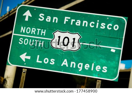 A green US 101 North/South highway sign with the freeway in the background - stock photo