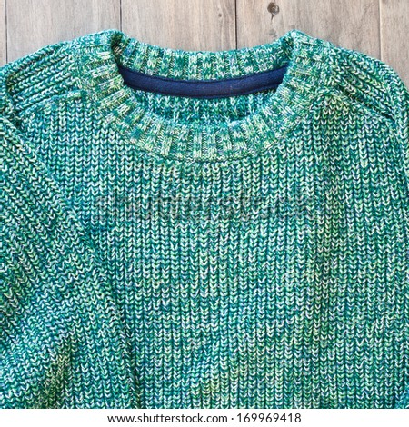 A green wool jumper on a wood surface - stock photo
