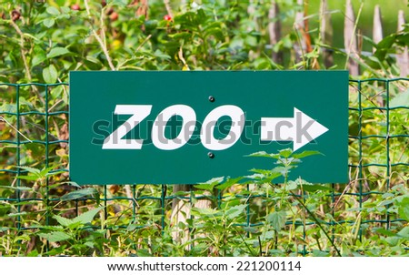 A green zoo' sign on a green fence - stock photo