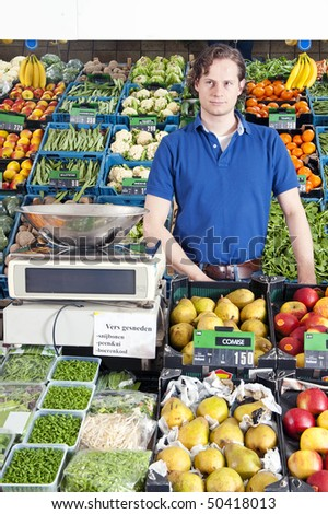 A greengrocer standing behind the display counter surrounded by fresh fruit and vegetables - stock photo