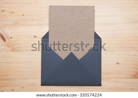 A grey envelope on the wood desk, top view at the studio. - stock photo