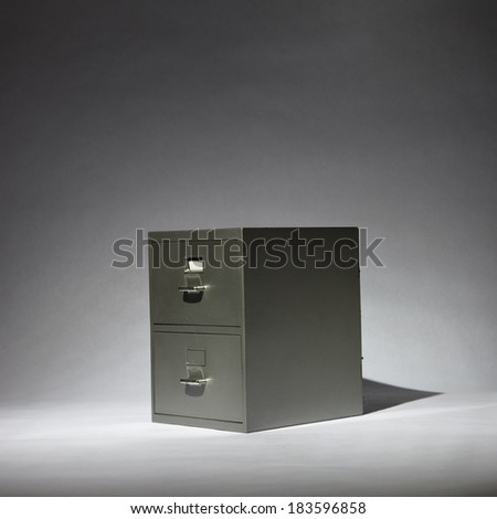 A grey filing cabinet in a spotlight. - stock photo