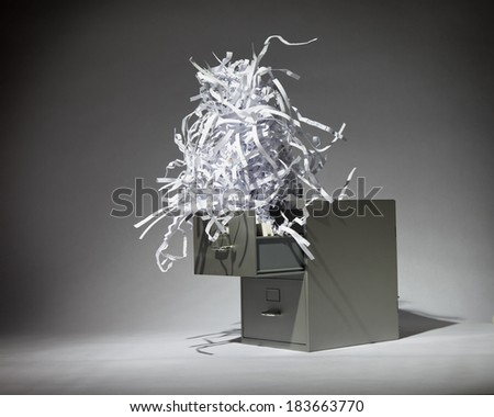 A grey filing cabinet with a bunch of shredded of paper coming out of the top drawer. - stock photo