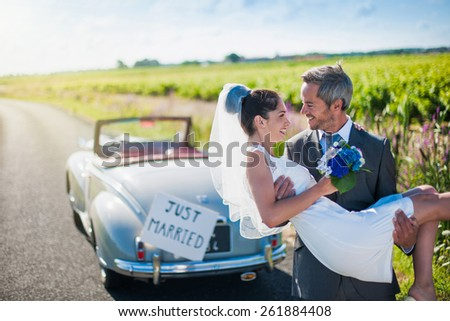 A grey hair groom is carrying is bride in his arms on a country road close to their vintage car. - stock photo