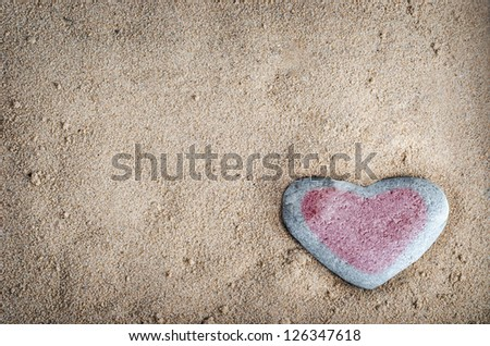 A grey heart shaped stone on grainy sand, tinted with a pinkish red heart.  This version is vignetted and edited to give a retro or lo-fi appearance. - stock photo