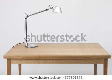 A grey retro aluminum lighting stand on the wood table(desk)