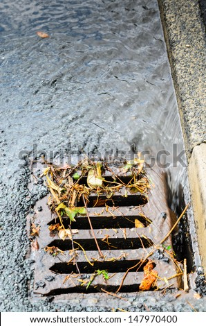 A grid/drain in the UK showing heavy rain draining away with debris - stock photo