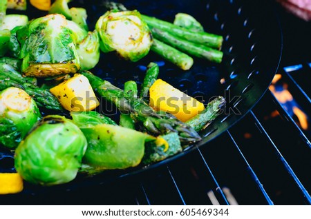 A grill pan with asparagus, zucchini, brussel sprouts and more.