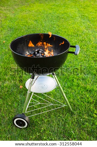 A grill with burning charcoal in it, on a lawn.
