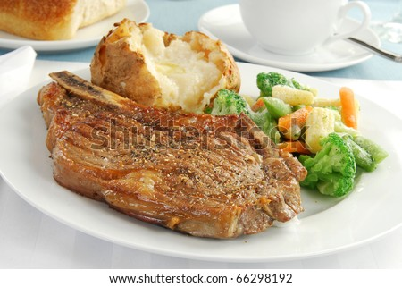 A grilled rib eye steak with a baked potato