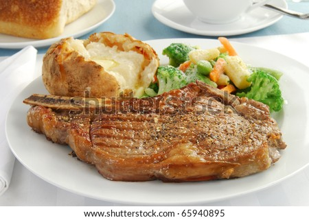 A grilled rib eye steak with baked potato and mixed vegetables - stock photo
