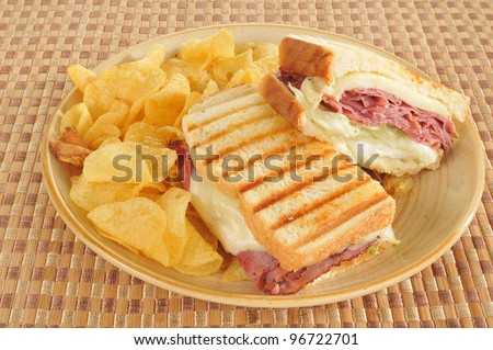 A grilled roast beef and swiss panini with potato chips