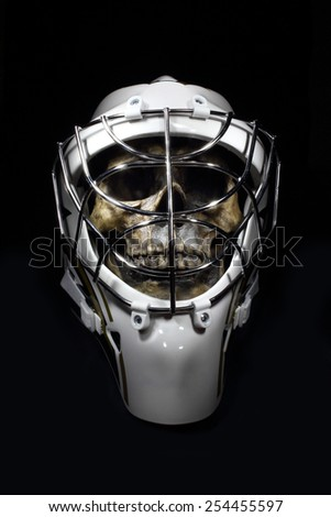 A grinning skull wears a hockey goalie mask.