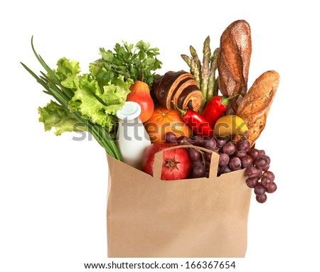 A grocery bag full of healthy fruits and vegetables / studio photography of assorted foods in brown grocery bag isolated over white background