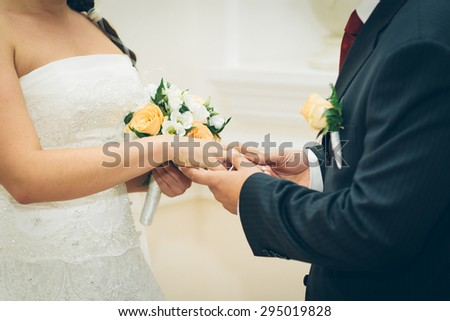 A groom gently holding his beautiful brides hand - stock photo
