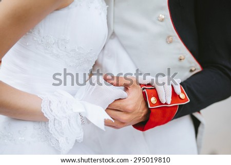 A groom in a hussar uniform gently holding his wifes hand