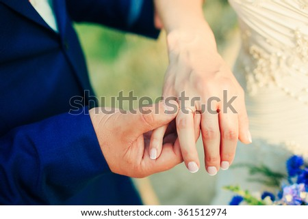 a groom is wearing a ring on a bride's finger, close shot, wedding photo