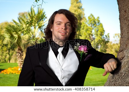 A groom leans on a tree on his wedding day.  He has a pink rose boutonniere, a white vest and tie, silver, diamond shaped earrings, and long hair. - stock photo