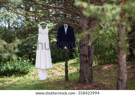 A groom's suit and a bride white dress on the wedding day. - stock photo