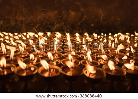 A ground of burning candles lighting up with shallow depth of field at buddhist temple in Kathmandu,Nepal. Lighting up candles for praying and faith purpose - stock photo