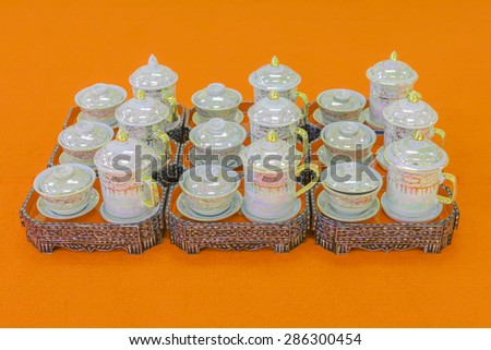 A group ceramic tea set in white gold pattern on a orange background. - stock photo