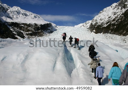 A group hikes up fox glacier - New Zealand. - stock photo