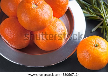 a group mandarins on a metal plate for sweets near other clementines filter  haze