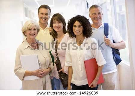A group of adult students with backpacks standing in a campus corridor - stock photo