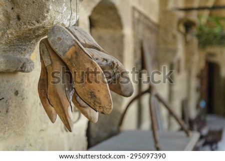 A group of antique wooden shoe forms hanging in an outdoor Mediterranean market. - stock photo