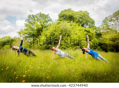 A group of beautiful young european girls doing yoga class in the summer fresh forest.