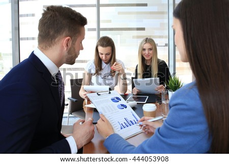 A group of business people at a meeting on the background of office. Focus on a beautiful bussineswoman - stock photo