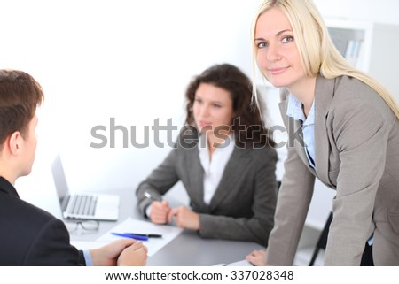 A group of business people at a meeting on the background of office. Focus on a beautiful blonde