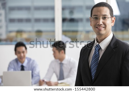 A group of business people lead by a happy caucasian Business man.
