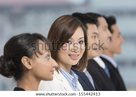 A group of business people lead by a happy Chinese Businesswoman.