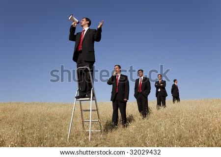 a group of businessman in the field getting in line for there time to speak - stock photo