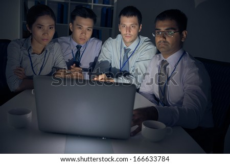 A group of businesspeople working before deadline in the night - stock photo