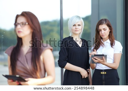 a group of businesswomen from tablets on the street