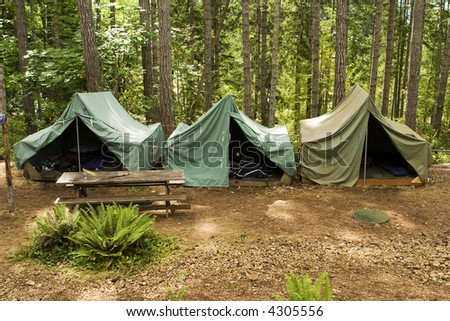 A group of canvas tents at a campground at the Camp Parsons boy scout camp in Washington. Some of the scouts' things like sleeping bags are just visible through the open tent flaps. - stock photo