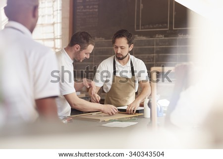 A group of carpenters making frames in a workshop - stock photo
