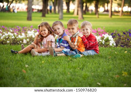A group of children relaxing and playing in the park on the green grass.
