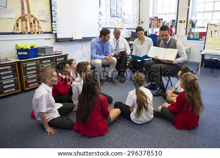 A group of children sit on the floor cross legged, listening to a group of teachers read a story. - stock photo