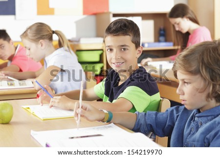 A group of children sitting in the classroom and writing - stock photo