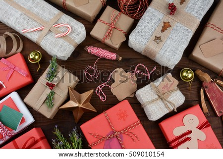 A group of Christmas presents on a dark wood table.