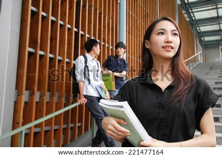 A group of college friends sitting holding books on campus - stock photo