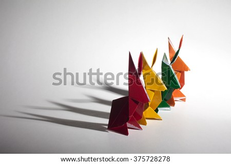 A group of colored origami paper rabbits with long shadows.