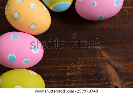 A group of colorful easter eggs on a wooden plank background - stock photo