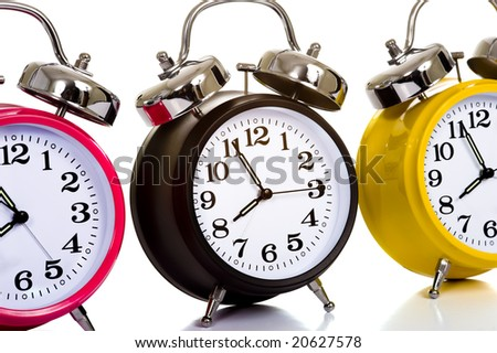 A group of colorful, traditional alarm clocks on a white background, time concept