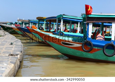 A group of colourful boats moored at Hoi An - Vietnam. Boats such as these are iconic of the seaside port of Hoi An in Vietnam. Hoi An is a popular tourist destination in Vietnam.